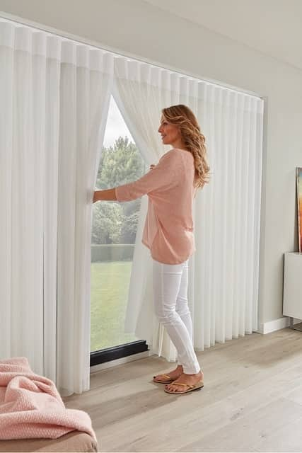 A woman opening white curtains in a living room